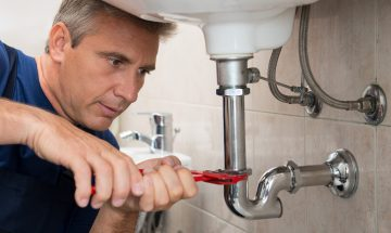 Closeup Of Male Technician Fixing Sink Pipe In a Bathroom