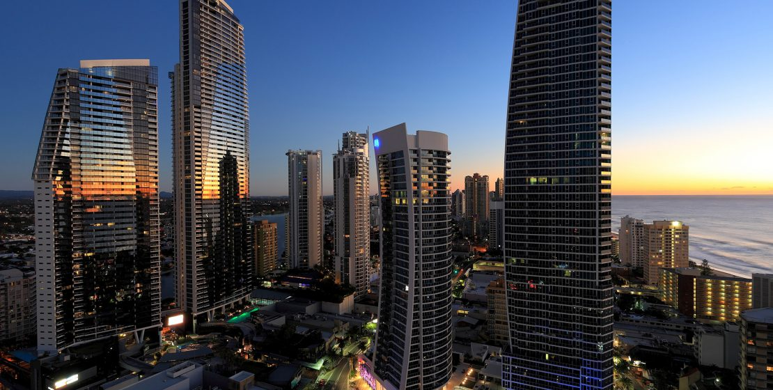 The skyline of a city with tall modern buildings at dusk.  The ocean is visible in the background.  The sky is clear blue with lines of yellow, orange and white on the horizon reflecting in the glass of the buildings.